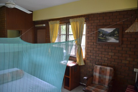 Simple brick-finished rooms with mosquito net.