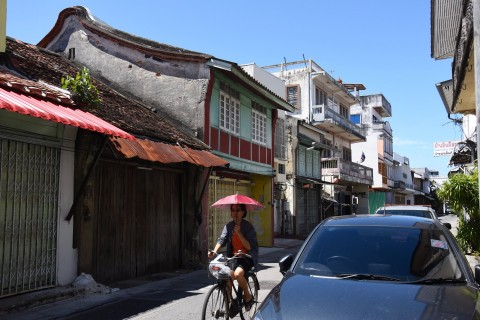 A woman rides a bike through Songkhla's old town. Photo taken in or around Songkhla, Thailand by David Luekens.