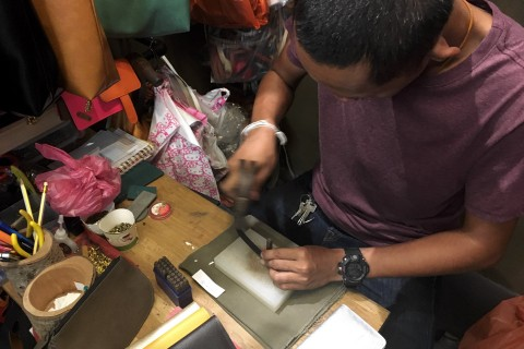Craftsman at work. Get your name added to any leather bag, wallet, passport holder...  Photo taken in or around Chatuchak weekend market, Bangkok, Thailand by Samantha Brown.