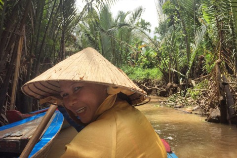 Paddling with a smile. Photo taken in or around Mekong Delta boat trip, My Tho, Vietnam by Cindy Fan.